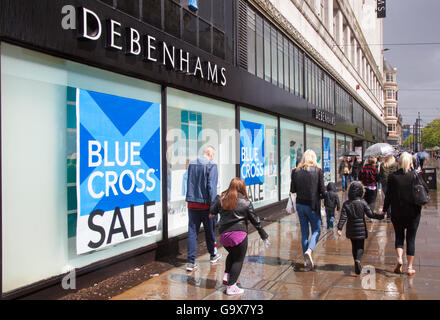 Out of focus blurred shoppers, people walking figures passing Blue Cross Summer Sale signs at Debenhams Store in - Stock Photo