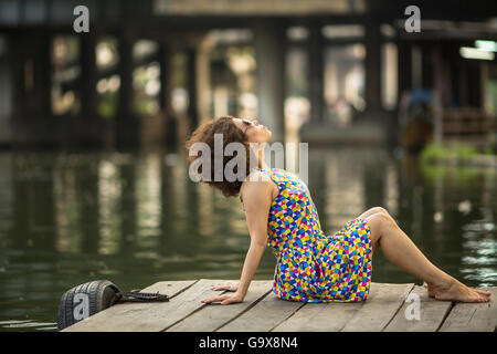 Spectacular young asian girl is sitting on a river dock. - Stock Photo