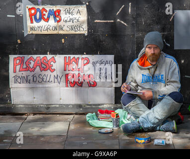 Helping the homeless. A rough sleeper, seated man not begging, but writing poems, trying to sell them. Cardboard - Stock Photo