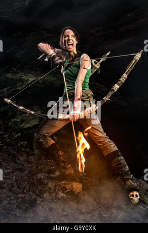 Rise of the Tomb Raider. screaming woman dressed up as Lara Croft holds a bow and pulls the bowstring with a burning - Stock Photo