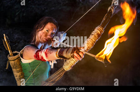Rise of the Tomb Raider. Woman dressed up as Lara Croft aiming with a bow and pulls the bowstring with a burning - Stock Photo