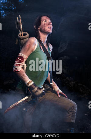 Rise of the Tomb Raider. Woman dressed up as Lara Croft stands next to the caves, holding a knife in the hand. - Stock Photo