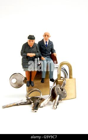 Miniature figurines of elderly couple sitting on padlocks - Stock Photo