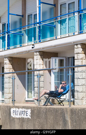 Young man enjoying the sunshine sitting on balcony of beach huts at Branksome Dene Chine, Poole in July - Stock Photo