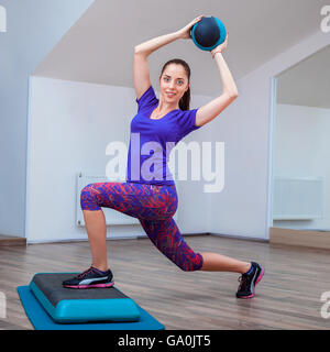 Fitness girl, wearing in sneakers posing on step board with ball - Stock Photo