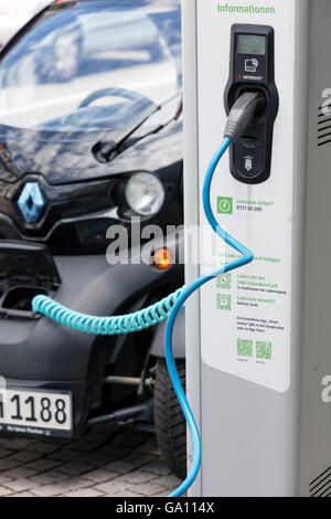 Electric car, Renault, being recharged at plug-in station in front of modern office building. - Stock Photo
