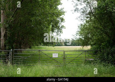 Locked galvanised gates leading to a tree-lined field and a sign stating that this is private land - Stock Photo