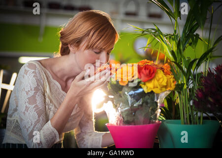 Female florist smelling rose flowers - Stock Photo