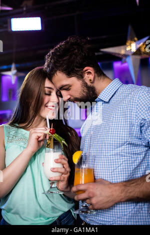 Couple embracing each other at bar counter while having cocktail - Stock Photo