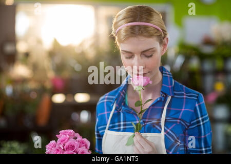 Female florist smelling pink rose - Stock Photo