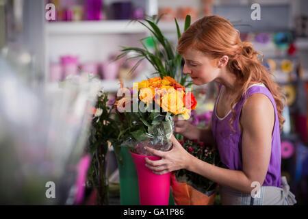 Female florist smelling flower bouquet - Stock Photo
