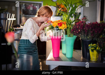 Portrait of female florist smelling rose flowers - Stock Photo