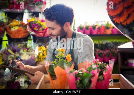 Male florist writing and making notes - Stock Photo
