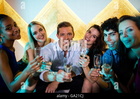 Group of smiling friends sitting on sofa and having a glasses of champagne - Stock Photo