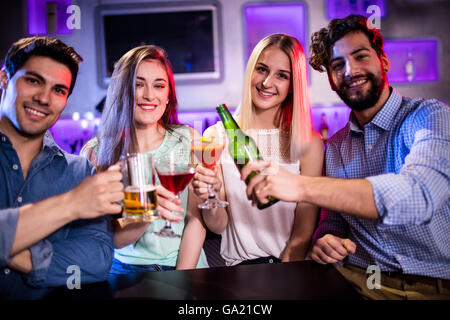 Group of friends toasting cocktail, beer bottle and beer glass at bar counter - Stock Photo