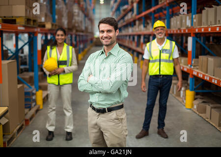 Focus on manager is posing with crossed arms in front of his workers - Stock Photo