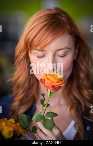 Female florist smelling a rose flower - Stock Photo