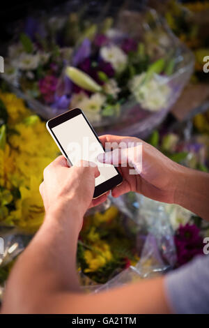 Male florist text messaging on mobile phone - Stock Photo