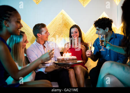 Group of smiling friends having a glass of champagne while celebrating birthday - Stock Photo