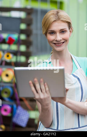 Happy female florist using digital tablet - Stock Photo