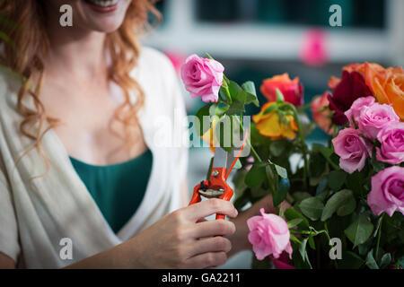 Female florist preparing flower bouquet - Stock Photo
