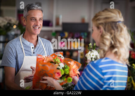Florist giving bouquet of flower to customer - Stock Photo