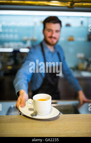Waiter offering cup of coffee - Stock Photo