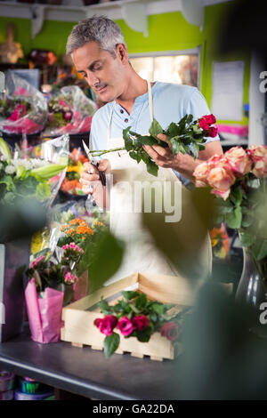Male florist trimming stems of flowers - Stock Photo