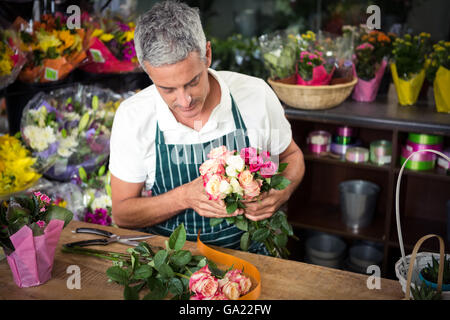 Male florist holding bunch of roses - Stock Photo