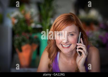 Female florist using mobile phone - Stock Photo