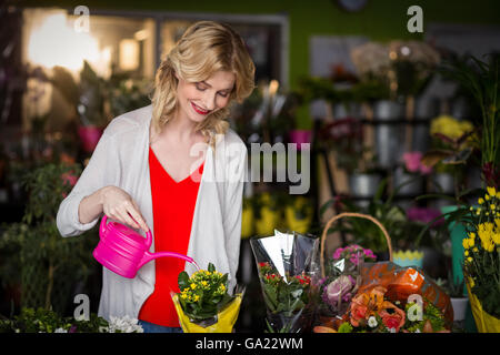 Female florist watering flowers - Stock Photo