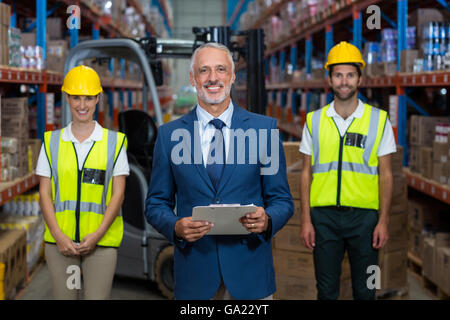 Focus of happy manager is posing in front of the workers - Stock Photo