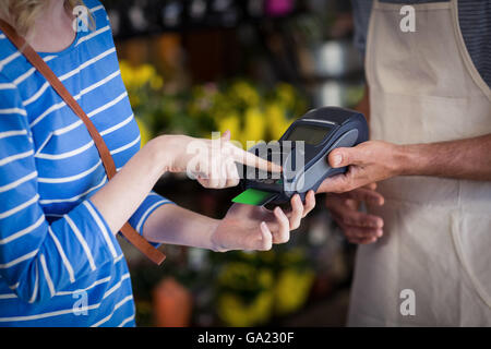 Woman making payment with her credit card to florist - Stock Photo