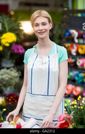 Happy female florist standing in flower shop - Stock Photo
