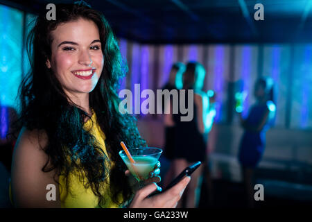 Beautiful woman using mobile phone while having cocktail - Stock Photo