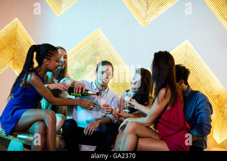 Group of smiling friends sitting on sofa and having a glass of champagne - Stock Photo