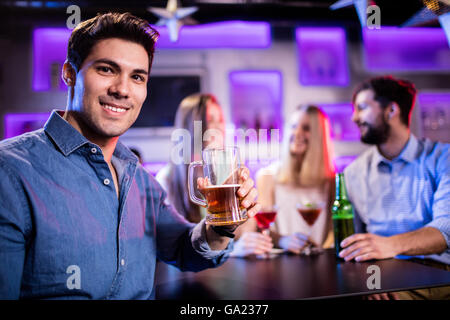 Portrait of young smiling man having glass of beer at bar counter - Stock Photo