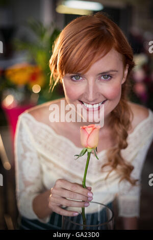 Portrait of female florist smelling a rose flower - Stock Photo