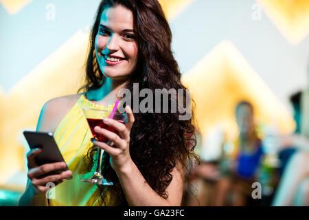 Beautiful woman using mobile phone while having red martini - Stock Photo