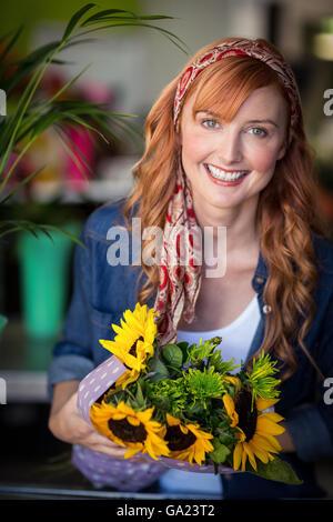 Smiling female florist holding bunch of flower - Stock Photo