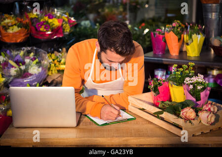 Male florist noting order in notepad - Stock Photo