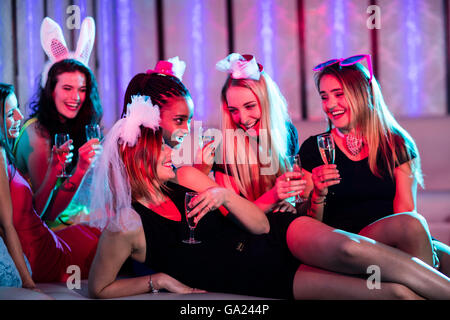 Group of women interacting while having a glass of champagne - Stock Photo
