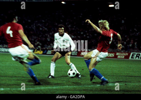 Czechoslovakia 's Anton Ondrus (l) and Jan Capkovic (r) with West Germany's Dieter Muller (c)