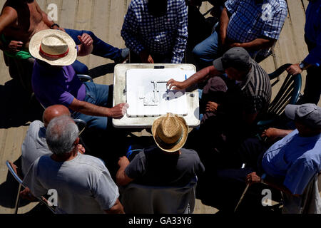 A group of men watch as two domino players play on the Platja Nova Icaria beach in Barcelona. - Stock Photo