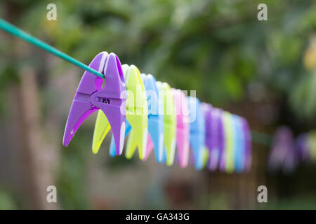 Colourful clothes peg on a washing line with beautiful bokeh. - Stock Photo