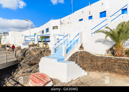 Typical white Canarian houses in Puerto del Carmen town on coast of Lanzarote island, Spain - Stock Photo