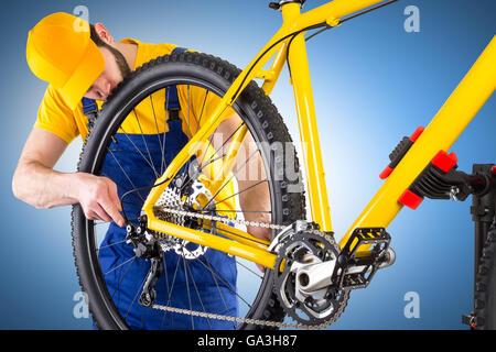bicycle mechanic working on yellow mountain bike - Stock Photo