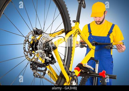 bicycle mechanic straightening handlebar on mountain bike - Stock Photo