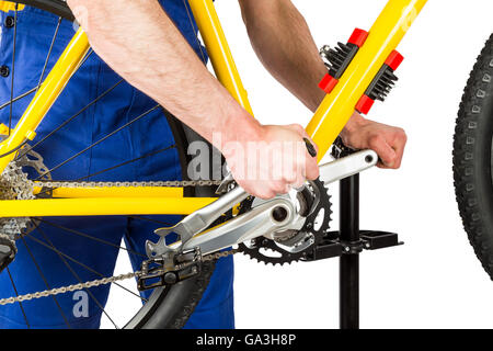 bicycle mechanic tightening pedal on mountain bike - Stock Photo
