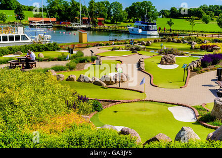 Berg, Sweden - June 20, 2016: The miniature golf course with the marina in the background. People photographing - Stock Photo